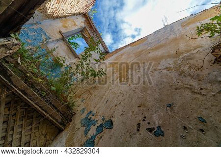 Abandoned Dormitory Building Interior With Large Shabby Wall And No Roof With Blue Sky And White Clo