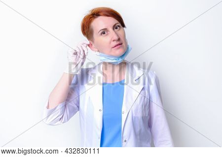 Young Woman In White Medical Gown Takes Off Her Medical Mask. Portrait Of Female Doctor On White Bac