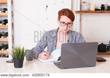Young Woman With Short Hair In Glasses And Shirt Looks Attentively At Laptop Screen And Makes Notes