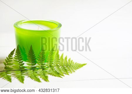 Green Scented Candle With Fern And Natural Fragrance On A White Background. Aromatherapy, Relaxation