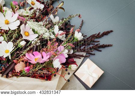 Fresh Bouquet Of White Pink Flowers With Burgundy Foliage Wrapped In Paper And Arranged On Grey Back