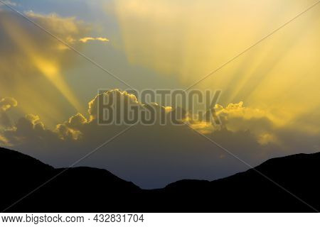 Sunbeam Shining Trough Cloudy Sky Before Sunset To Mountain Range