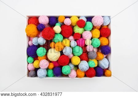 A Lot Of Multi-colored Wool Balls Of Knitted Yarn In A Cardboard Box On A White Background.the Conce
