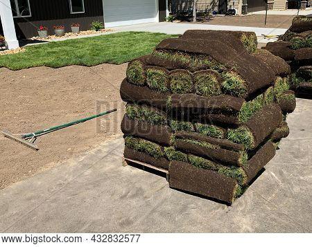 Rolls Of Fresh Sod Grass Piled On Wood Pallets For Installation, And Trimmed Pieces, At A New Home.