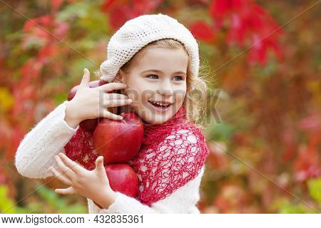 Beautiful Little Girl Holding Apples In The Autumn Garden. . Little Girl Playing In Apple Tree Orcha