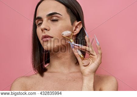 Sensual Androgynous Young Transgender With Dark Brown Hair Using Rose Quartz Roller For Facial Massa