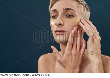 Close Up Portrait Of Young Transgender Applying Under Eye Gel Patches, Taking Care Of Skin While Pos