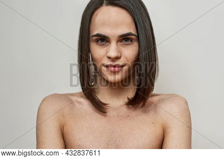 Androgynous Beautiful Young Transgender With Dark Brown Hairstyle Looking At Camera While Posing Iso