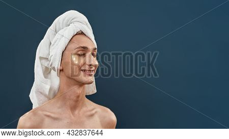 Naked Young Transgender With Applied Under Eye Gel Patches And Towel On Head Taking Care, Posing Wit