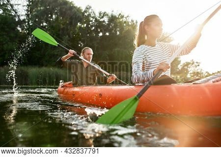 Young Caucasian Couple Having Fun In Leisure Activity, Paddling Together On River In Kayak. Leisure,