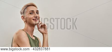 Portrait Of Happy Androgynous Transgender Young Man Holding Hand Near His Face And Smiling At Camera
