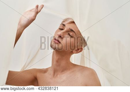 Portrait Of Sensual Young Transgender With Makeup Posing With Eyes Closed Isolated Over Light Pastel