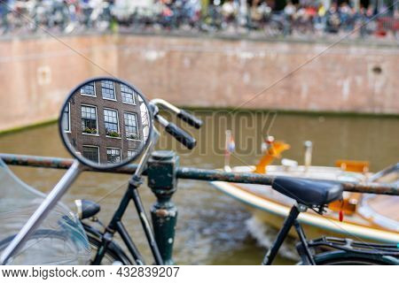 Bicycle Mirror Reflects Windows Of Building In Canal Background Blurry Canal Scene In Amsterdam, Net