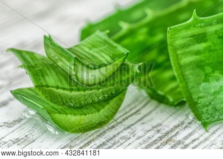 Pieces Of Aloe Vera With Pulp On A Wooden Background.aloe Vera Essential Oil Or Serum With Sliced Al