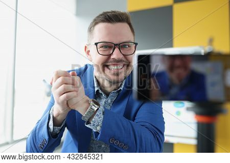 Young Satisfied Male Business Coach Clenching His Hands Into Fist In Front Of Mobile Phone Camera