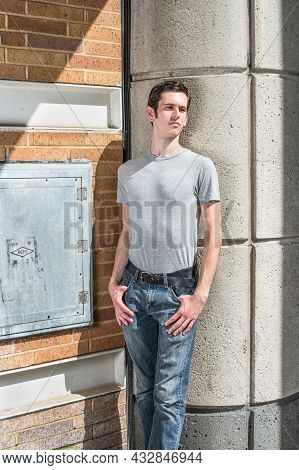 Dressing In A Gray T Shirt And Blue Jeans, A Young Handsome Guy Is Standing In A Corner Of The Stree