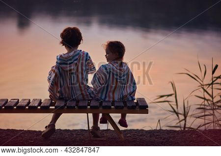 Cute Children, Siblings Sitting On The Bench By The Lake At Warm Summer Evening
