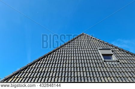 Open Roof Window In Velux Style With Black Roof Tiles And A Blue Sky Background.