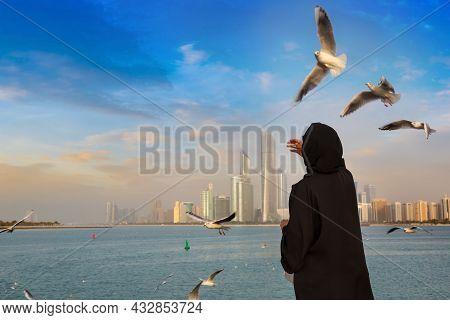 A Woman Wearing Arab Clothes Is Feeding Seagulls In Abu Dhabi In A Summer Day, United Arab Emirates