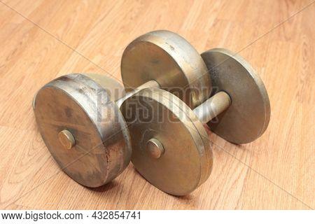 Heavy metal dumbbells and weights on wooden floor