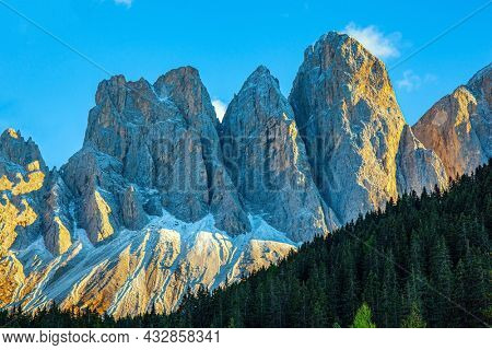 The majestic cliffs of the Dolomites rise picturesquely into the sky. Dolomites on a sunny autumn day. The clouds lit by the setting sun. South Tyrol.