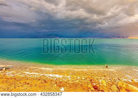 The Dead Sea is a closed salt lake. Israeli coast. Gloomy sky with dark thunderclouds. Magnificent exotic resort for treatment and relaxation. The smooth surface of the salt lake reflects the clouds
