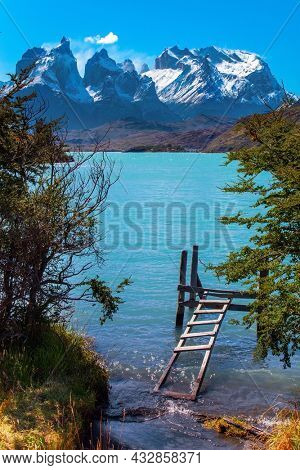 Travel to Chile. Picturesque lake Pehoe in the Patagonian Andes. The famous snow-capped cliffs of Los Cuernos by the lake. Huge lake with bright azure water from melting glaciers.
