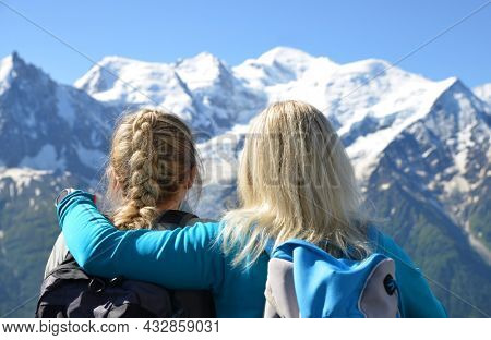 Hikers looking at the Mont Blanc from the summit of Le Brevent. French Alps, Chamonix, France.