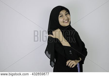 Smiling Young Asian Islam Woman Wearing Headscarf Is Smile And Pointing Behind.