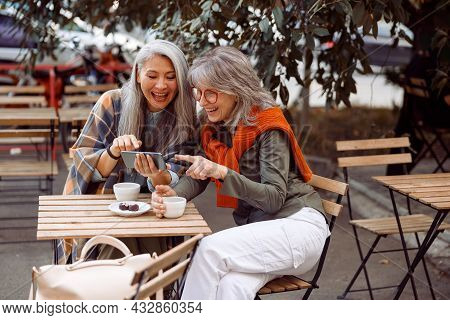 Positive Senior Asian Lady With Friend Surf Internet On Smartphone In Street Cafe