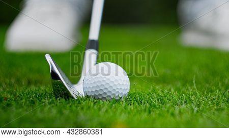 Golf club kicking the ball on green grass close up