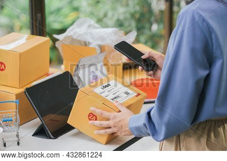 Online Seller Scan Parcel Bar Code On Shipping Box With Smartphone Using Mobile App. Business Woman
