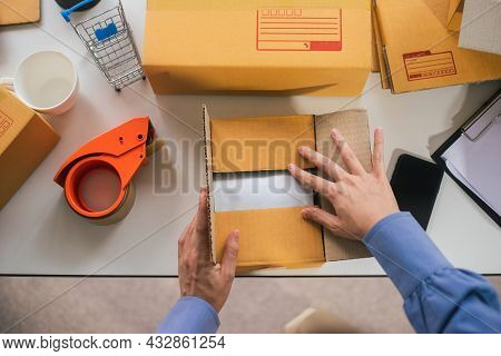 Top View Of Worker Or Seller Packing Product Ecommerce Shipping Order Box For Dispatching. Preparing