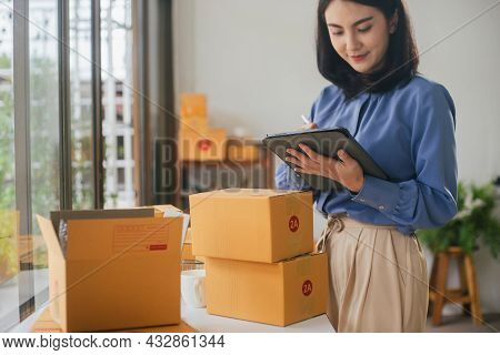 Business Asian Woman Use Tablet Checking Information On Parcel Shipping Box Before Send To Customer.