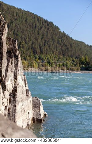 A Fast-flowing Wide And Full-flowing Mountain River. Large Rocks Stick Out Of The Water. Big Mountai