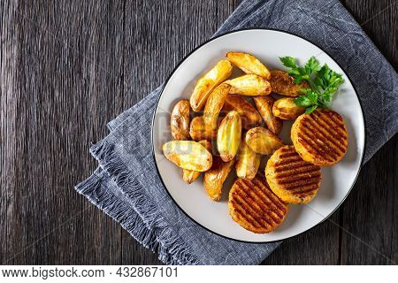Grilled Fish Burgers With Baked Potato Wedges On A Plate, Flat Lay