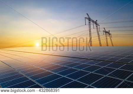 High Voltage Pylons With Electric Power Lines Transfering Electricity From Solar Photovoltaic Sells