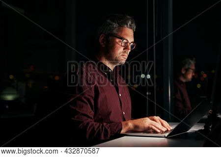 Serious Businessman Sitting Near Window Working On Laptop Late At Night In Office