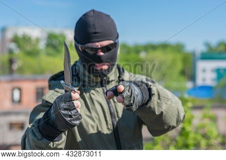 Street Bandit Threatens With A Knife And Shows A Pointing Gesture At Passers-by