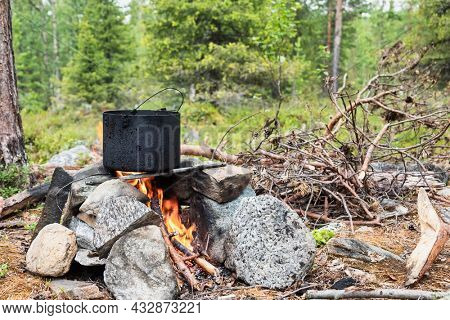 Cooking meal in a pot on burning campfire during wild camping in a forest