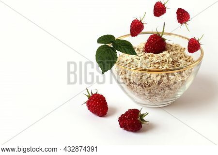 The Concept Of Proper Nutrition. Falling Raspberries In A Cup With Oat Flakes, Light Background, Clo