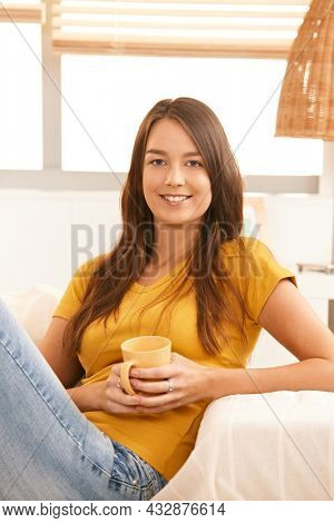 Portrait of attractive young woman sitting on couch at home holding coffee cup, looking at camera, smiling.
