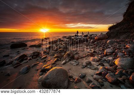 Anglers standing on the rock in Baltic Sea at sunrise, Gdynia. Poland