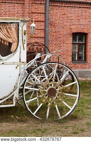 Old White Carriage On The Background Of A Red Brick Building