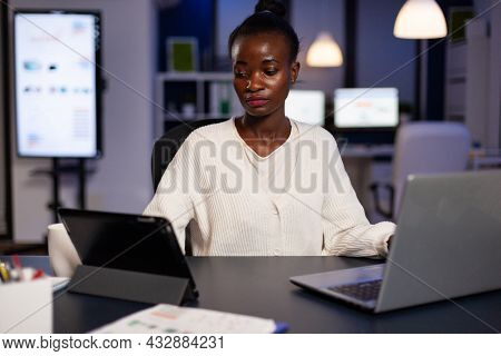 Workaholic Tired Multitasking African American Entrepreneur Analyzing Financial Graphs On Computer C