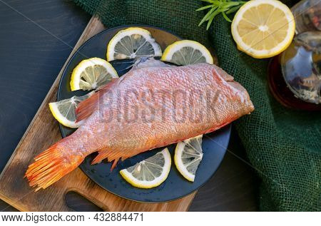 Red Snapper On A Plate With Raw Lemon