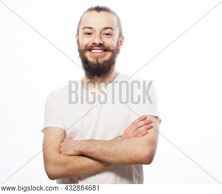 Lifestyle and people concept: Bearded young man wearing white t-shirt with his arms crossed over white background