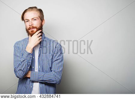Handsome young bearded man in smart casual wear looking at camera, over grey background