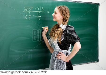 Girl Student Writing Some Math Equation At Blackboard. Cheerful Teenage Girl Student In Retro Soviet