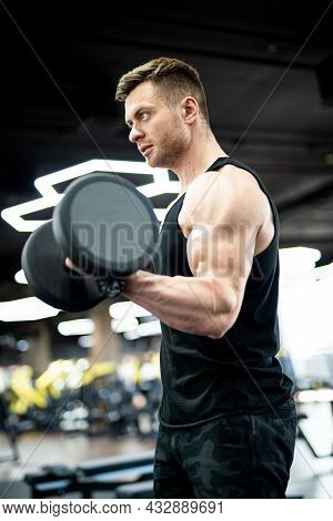 Muscular Athletic Man Training Hard In Gym. Handsome Strong Bodybuilder Doing Exercise.